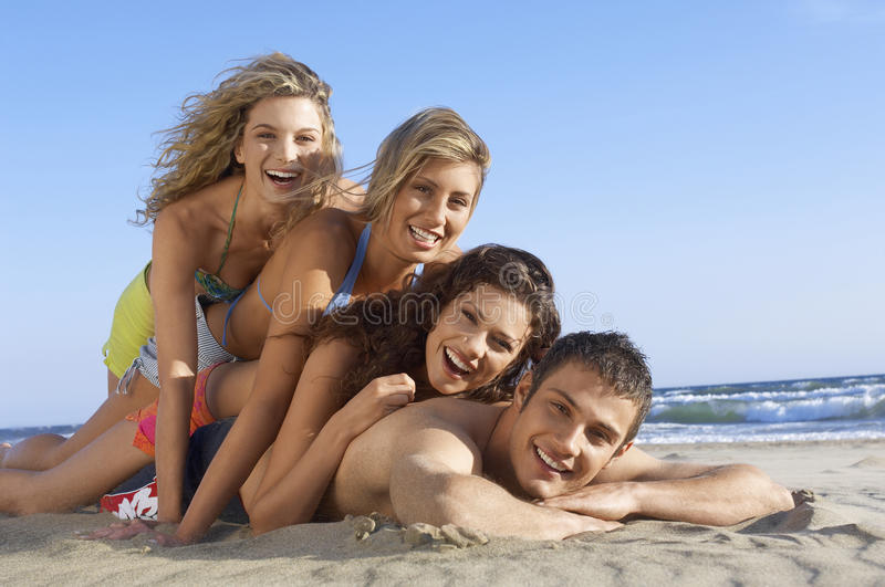 Friends Lying On Each Other At Beach Royalty Free Stock Photography