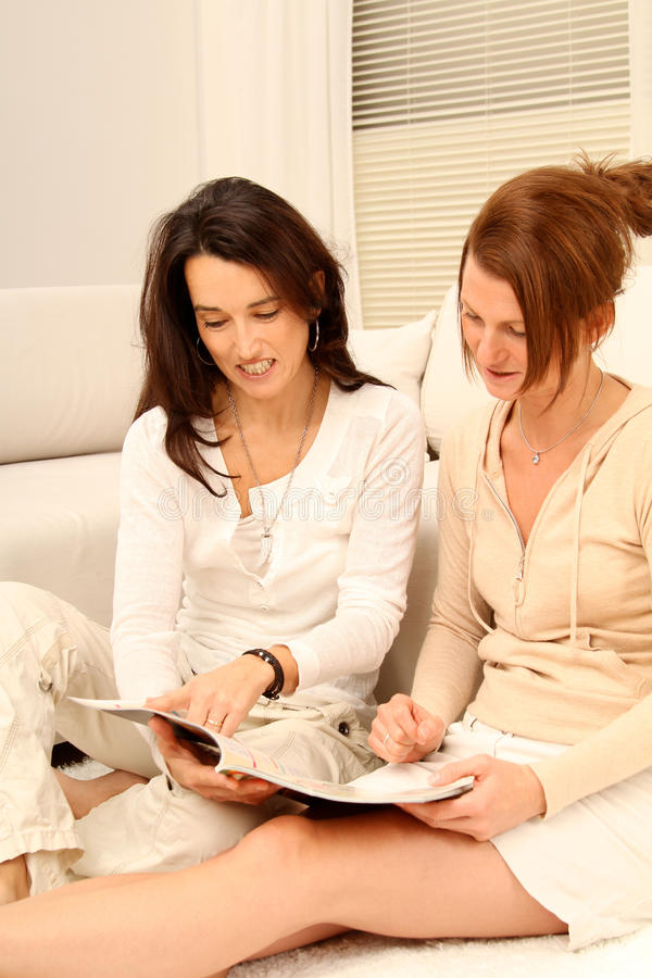 Friends with a magazine. Two girl-friends having fun while they reading a magazine together stock photo