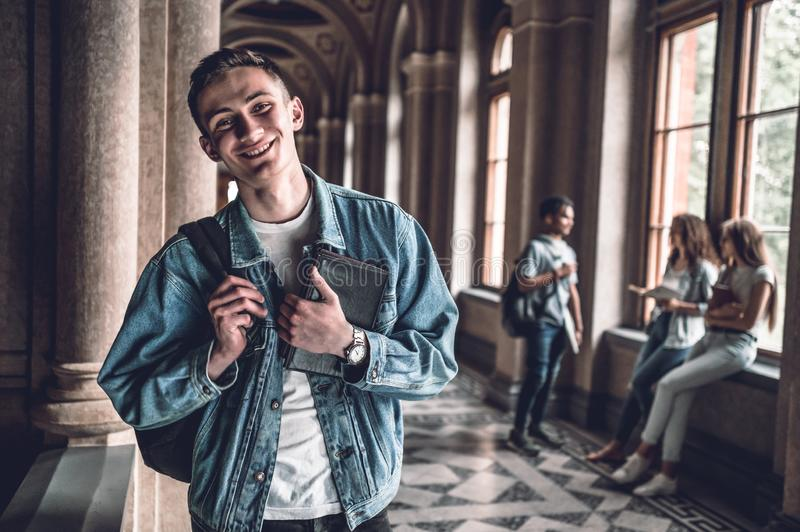 Friends make college fun.Portrait of a handsome young student with his friends in the background royalty free stock images