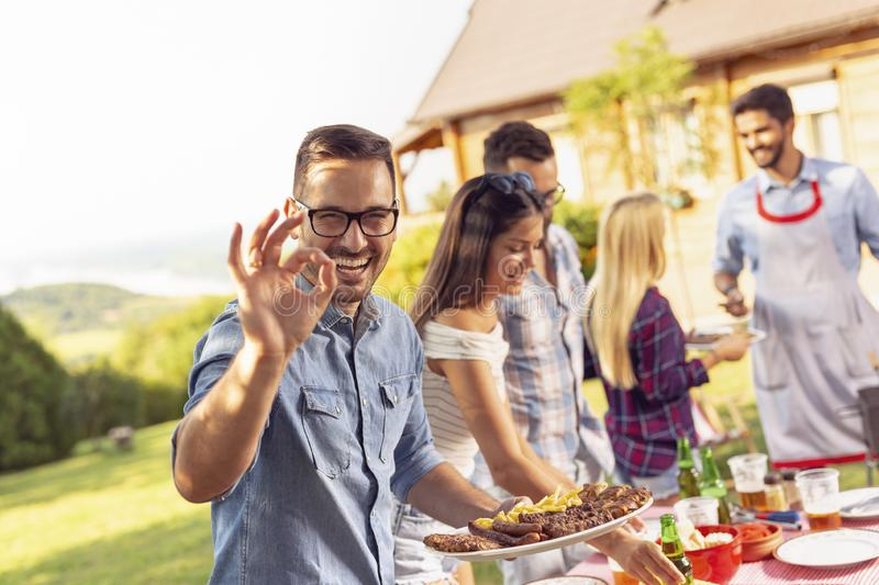 Friends making barbecue. Group of friends making barbecue in the backyard, drinking beer and having fun on a sunny summer day royalty free stock images