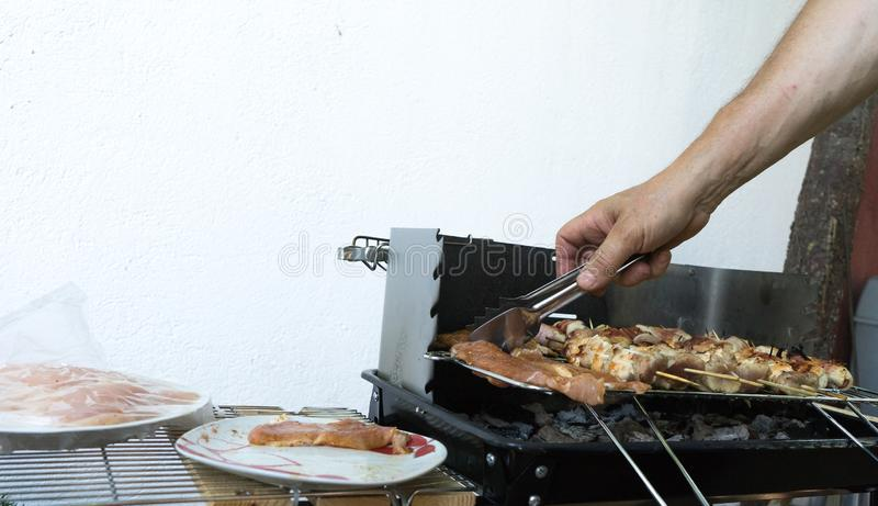 Friends making barbecue and having lunch. Close up of a man making barbeque. Frying meat in the outdoor setting. Grilled shish stock image