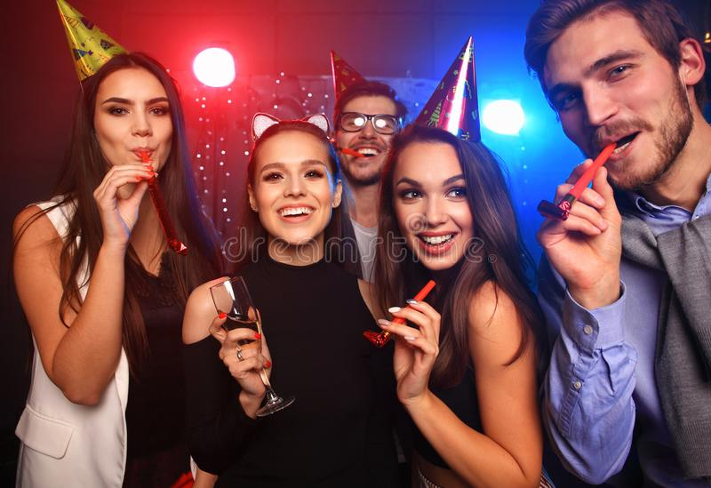 Friends making big party in the night. Five people throwing confetti and drinking champagne. stock images