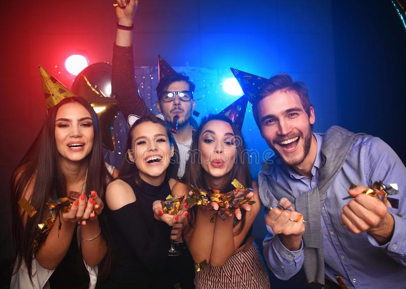 Cheerful young people showered with confetti on a club party. royalty free stock photography