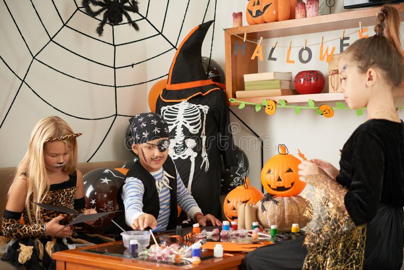 Friends making crafts for Halloween stock images