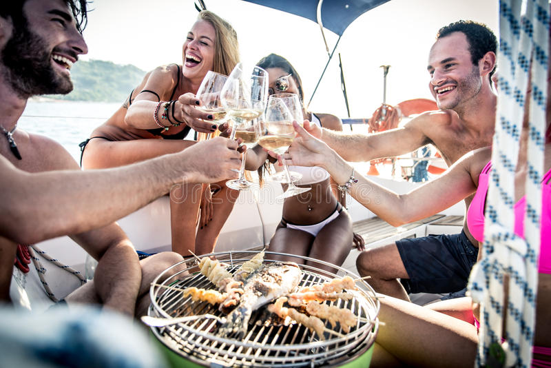 Friends making fish barbecue on the yacht stock photography