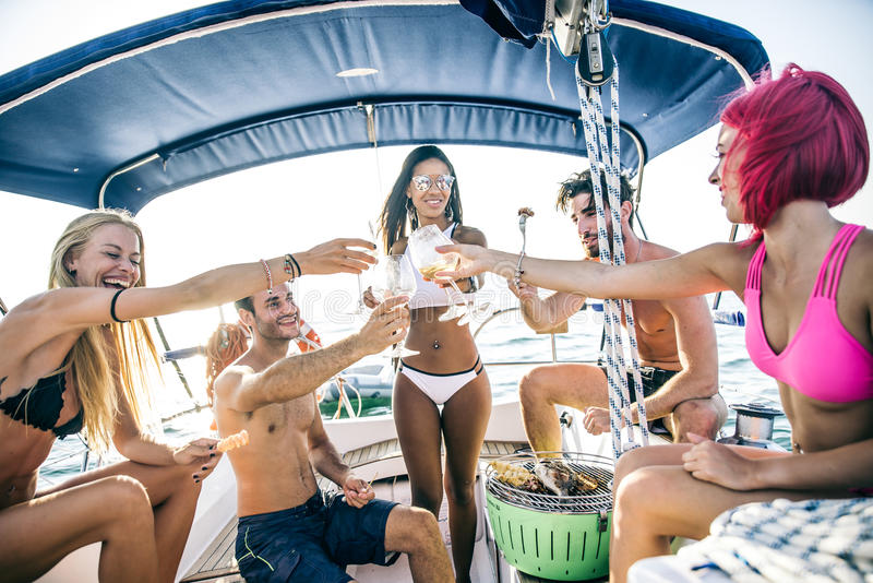 Friends making fish barbecue on the yacht royalty free stock images