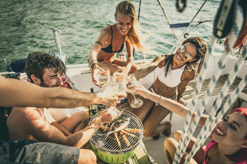Friends making fish barbecue on the yacht royalty free stock photography