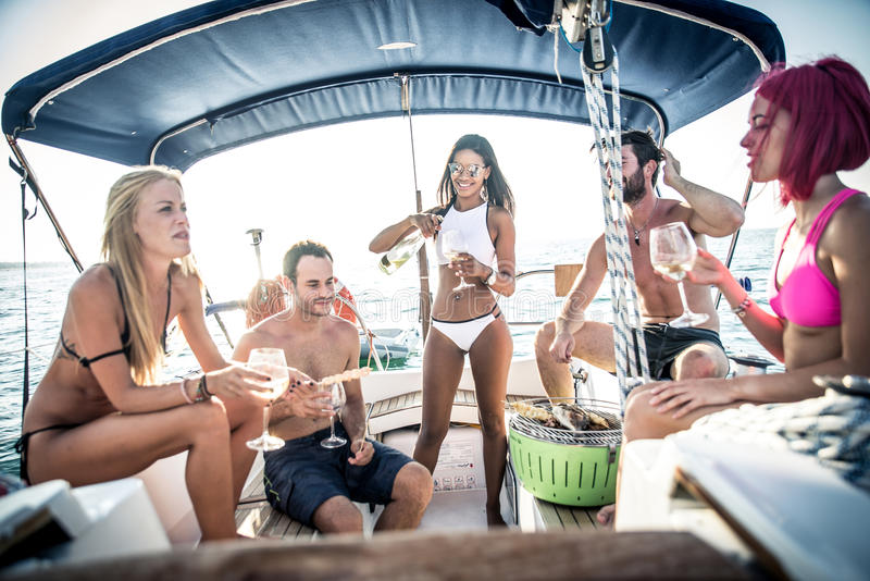 Friends making fish barbecue on the yacht stock image