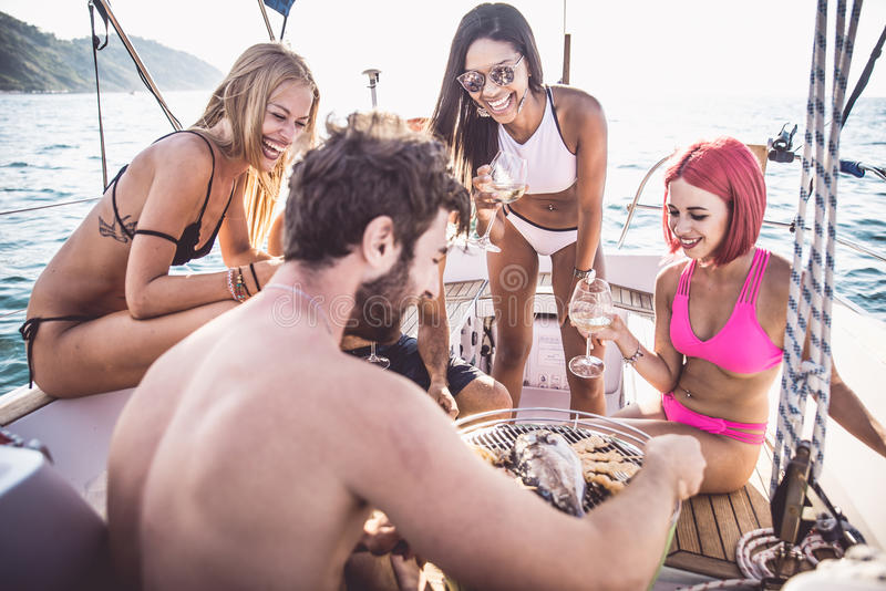 Friends making fish barbecue on the yacht stock photos