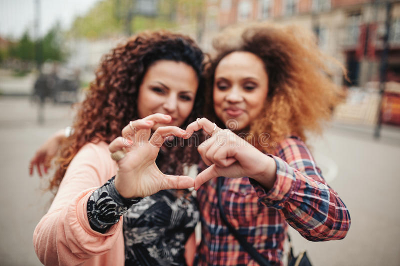 Friends making heart shape with fingers royalty free stock image