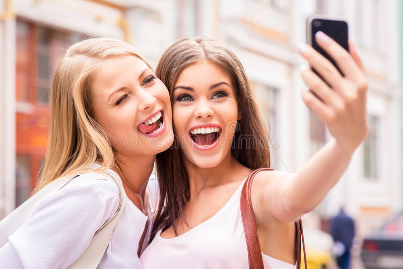 Friends making selfie. Two beautiful young women making selfie and grimacing stock photo