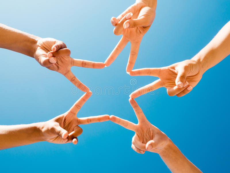Star fingers. Friends making a star with fingers against the sky stock photography