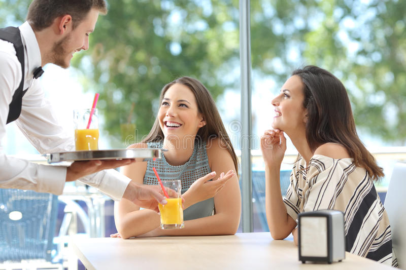 Friends meeting in a bar with a waiter serving royalty free stock image