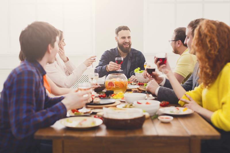 Group of happy people with wine glasses at festive table dinner party. Friends meeting. Group of happy people drink wine at party dinner table in cafe royalty free stock image