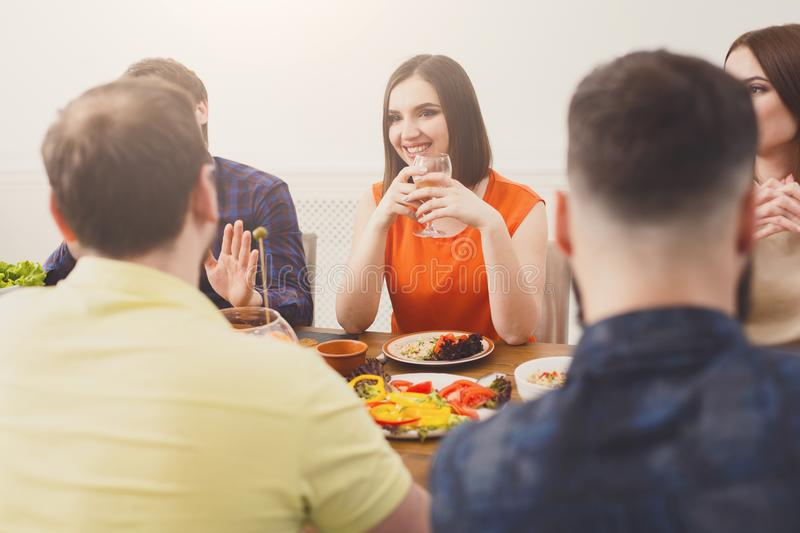 Pretty happy girl with friends at festive table dinner party royalty free stock images
