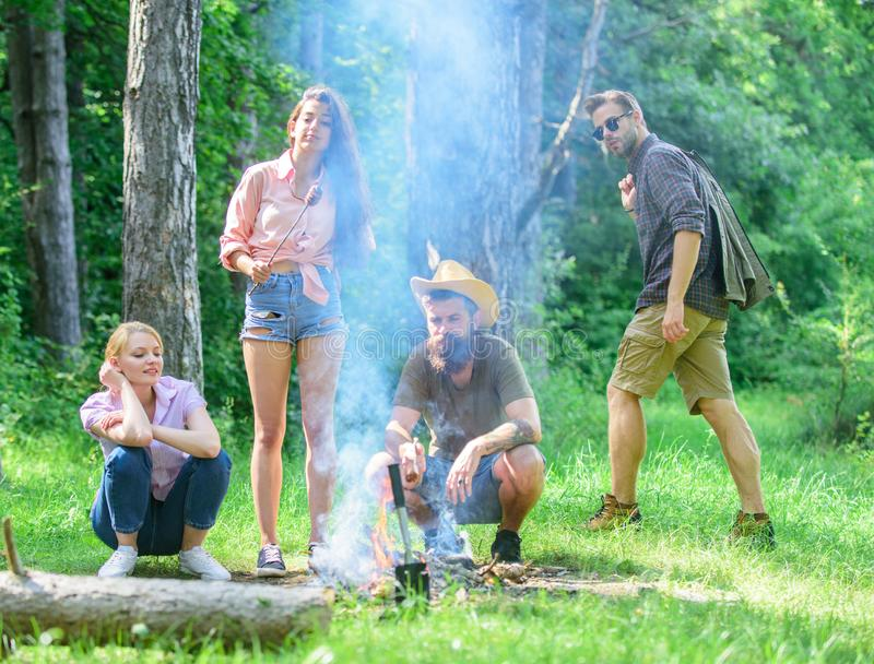 Friends meeting at meadow to hang out and prepare roasted sausages snacks nature background. Company having fun while. Roasting sausages on sticks. Gathering royalty free stock images