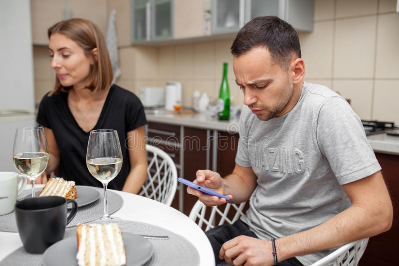 Friends meeting with wine and cake in the modern style kitchen. Young woman smile and joke. The man is focused on a mobile phone. Friends meeting with wine and stock photos