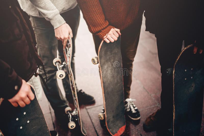 Group of friends skateboarders rest on the street stock photo