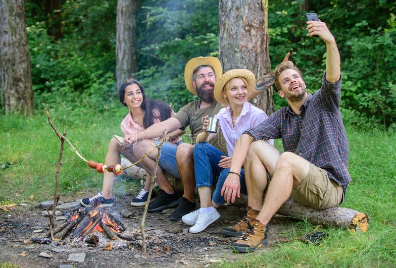 Friends near bonfire enjoy vacation and roasted food. Man taking photo near bonfire nature background. Tourists sit log. Near bonfire taking selfie photo stock photos