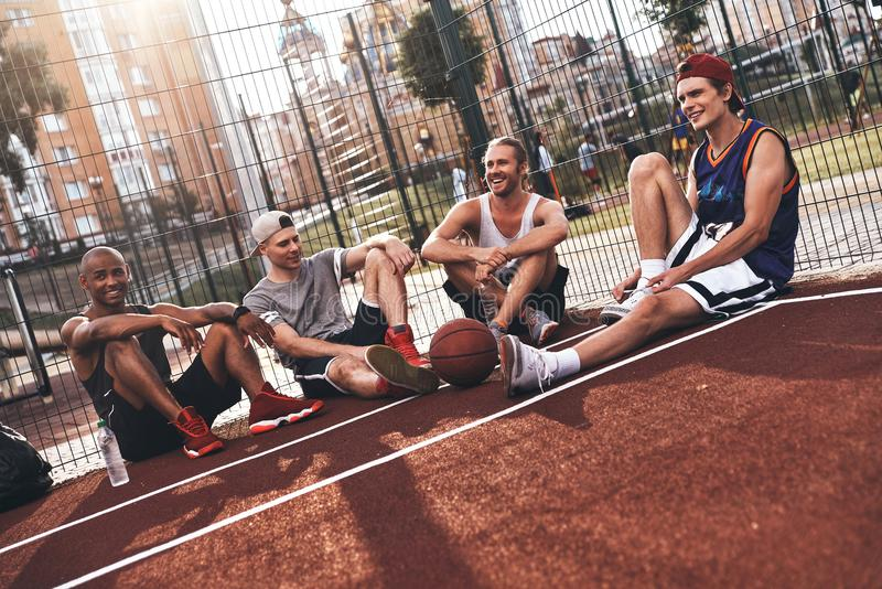 Friends no matter what. Group of young men in sports clothing smiling while sitting on the basketball field outdoors stock image