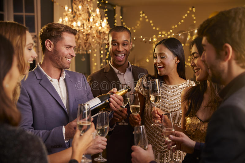 Download Friends Open Champagne As They Celebrate At Party Together Stock Photo - Image: 91321008