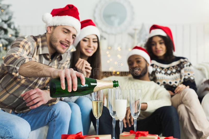 Friends open champagne while celebrating New Year royalty free stock photography