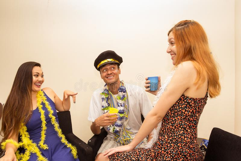 Friends are at a party. Celebrating the Brazilian Carnaval. Revelers are talking and drinking.. Multi ethnic group of friends are making Carnaval party stock photo