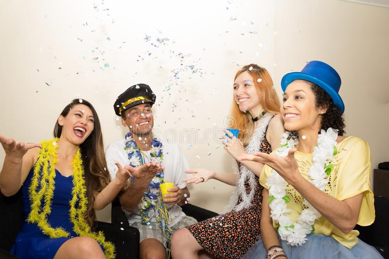 Friends are at a party. Celebrating the Brazilian Carnaval. Revelers play throwing confetti to the top.. Multi ethnic group of friends are making Carnaval party stock images