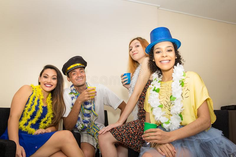 Friends are at a party. Celebrating the Brazilian Carnaval. Revelers are seated and looking forward.. Multi ethnic group of friends are making Carnaval party stock photography