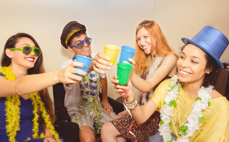 Friends are at a party. Celebrating the Brazilian Carnaval. Toast with colored cups.. royalty free stock image