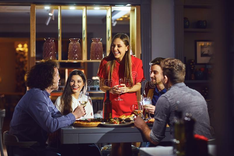 Friends at a party in a restaurant talking at the table stock photos