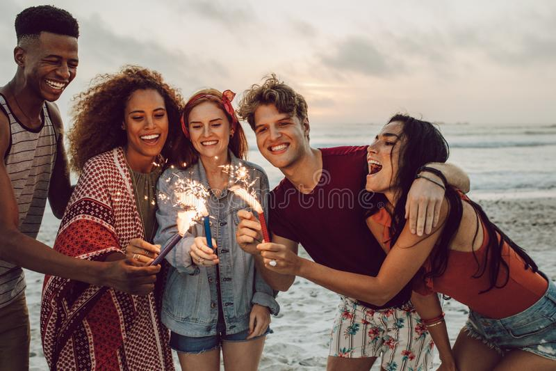 Friends partying on the beach with sparklers. Happy friends partying on the beach with sparklers. Multi-ethnic group of friends together at the beach celebrating stock photos
