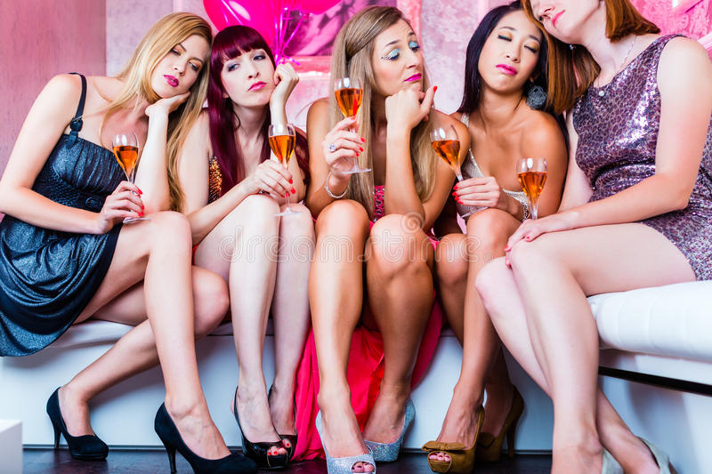 Friends partying in night club until sleep. Women partying with champagne in club until morning rise stock photography