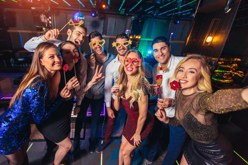 Friends partying in a nightclub make selfie photo stock images