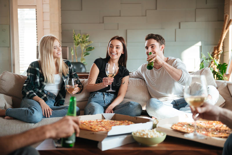 Friends with pizza, wine and beer talking and having fun. Group of cheerful young friends with pizza, wine and beer talking and having fun on sofa at home royalty free stock photos