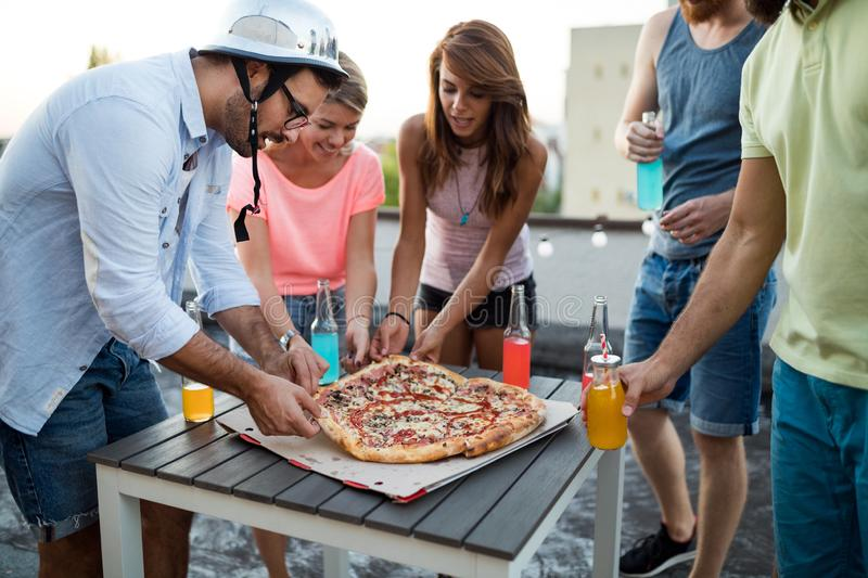 Friends and pizza. Young cheerful people eating pizza and having fun royalty free stock photo