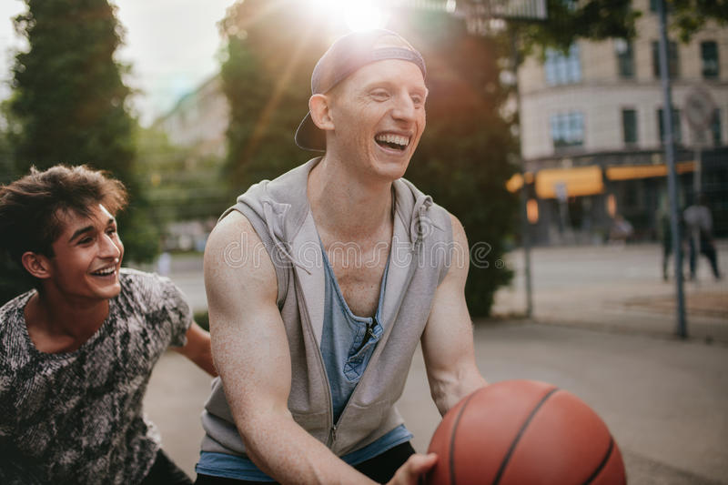 Two young friends playing basketball and having fun. Streetball players  having a game of basketball on court outdoors.