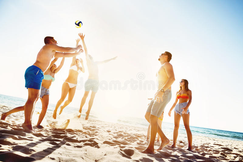 Friends playing beach voleyball sunset time stock image