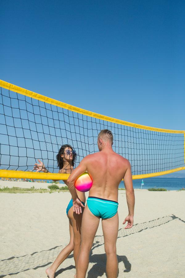 Friends playing beach volleyball sport. Woman and man having fun recreational volley ball game in summer living healthy stock photos