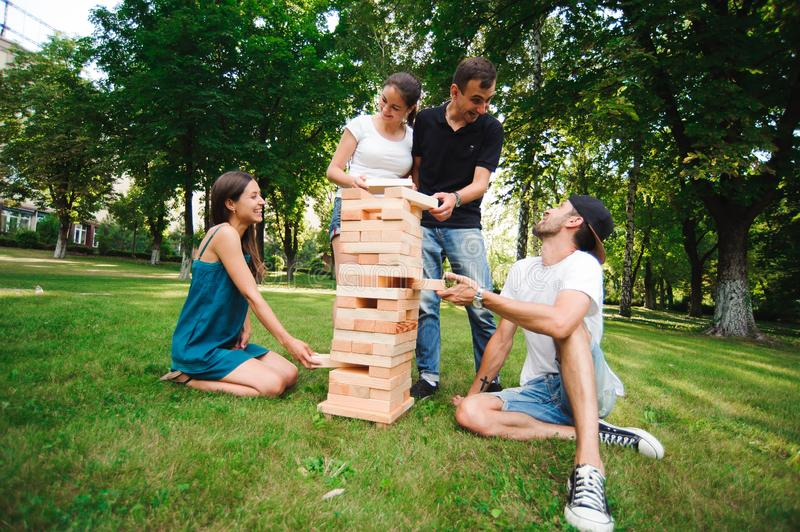 Friends playing board game. Giant Outdoor Block Game. Group game of physical skill with big blocks. royalty free stock image
