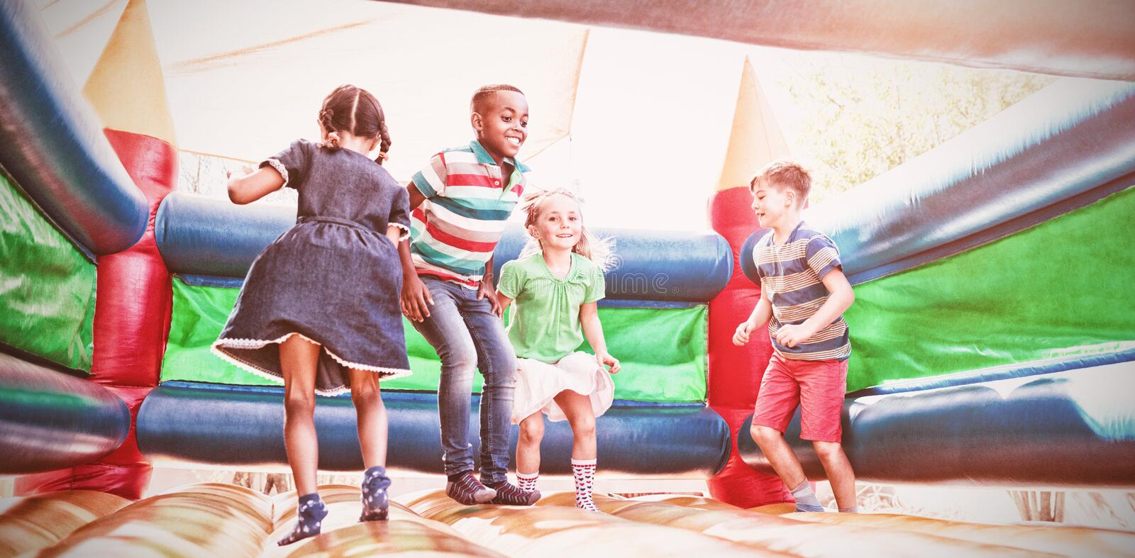 Friends playing on bouncy castle at playground royalty free stock photos