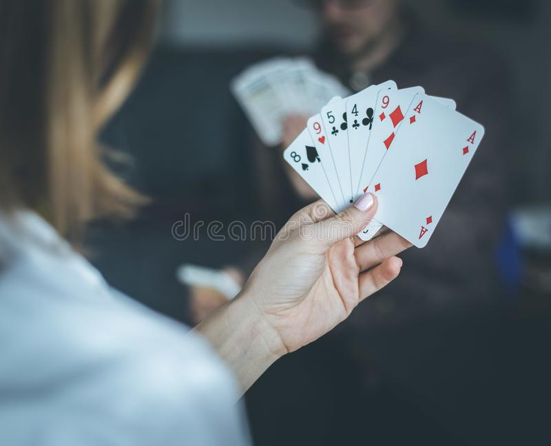 Friends are playing cards together at home. Woman is holding cards in her hands, man in the blurry background. Card playing at home: Friends are sitting on a stock photos