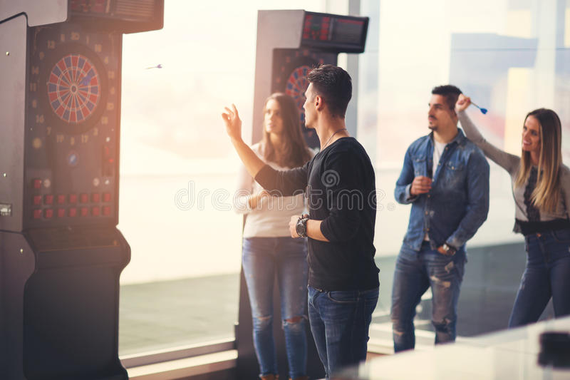 Friends playing darts in a club. Young friends playing darts in a club stock images