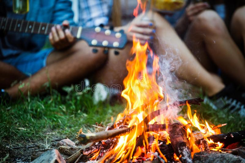 Friends playing music and enjoying bonfire in nature. Happy friends playing music and enjoying bonfire in nature stock photos