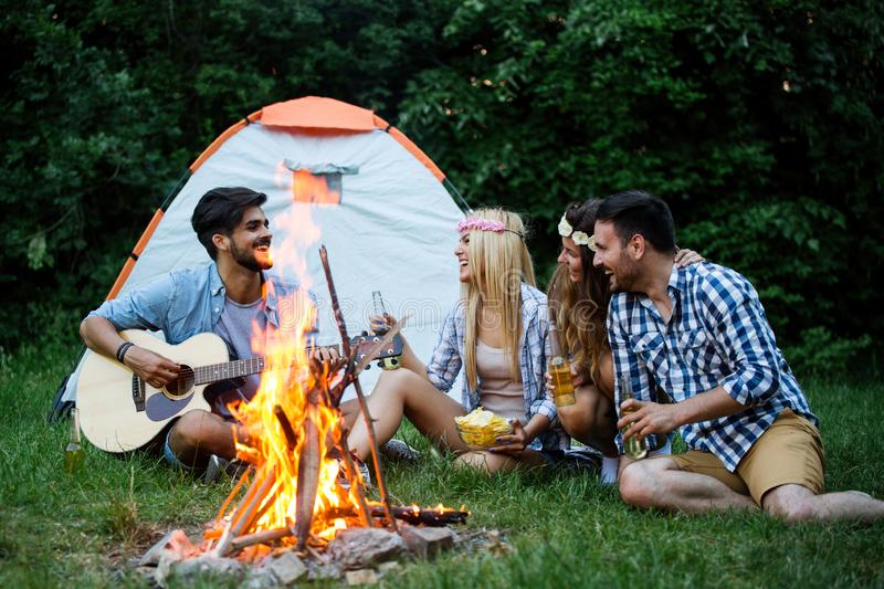Friends playing music and enjoying bonfire in nature. Happy friends playing music and enjoying bonfire in nature stock photography