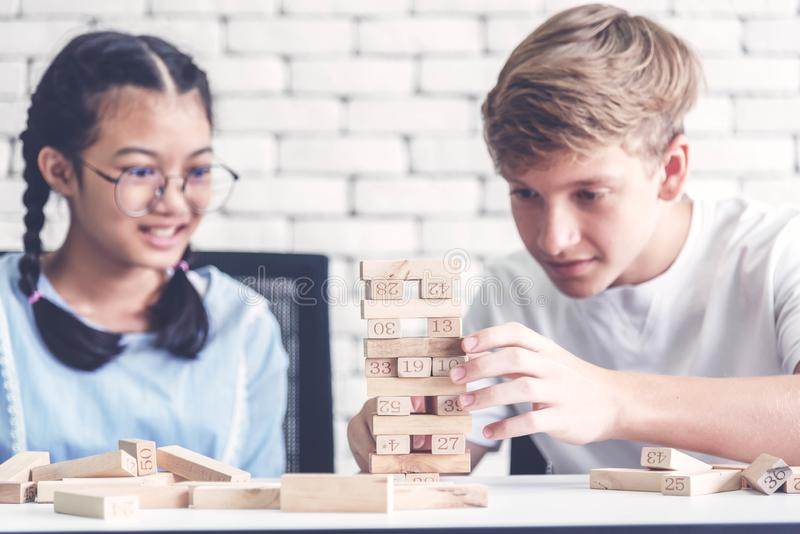 Friends playing stack of wooden cubes. Boys thinking how to win his friend on game. Plan and strategy concept stock photo