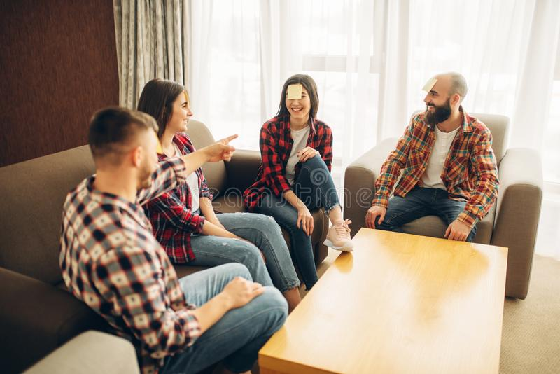 Friends playing sticker notes to forehead game. Funny friends playing sticker notes to forehead game. Company playing who I am at the table at home, people guess royalty free stock photos