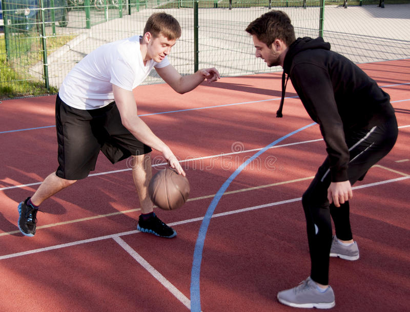 Friends playing street basketball. Two young friends playing street basketball on sunny day royalty free stock photography