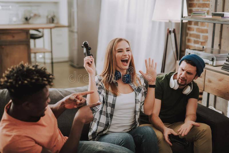 Friends playing video games and having fun while sitting on couch stock image