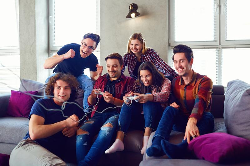 Friends playing video games in the room. Meeting friends stock photos